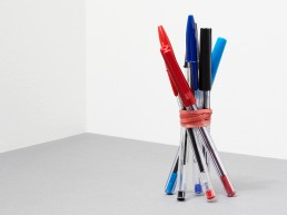 6 office pens of different colors, rubber banded together, and upright.